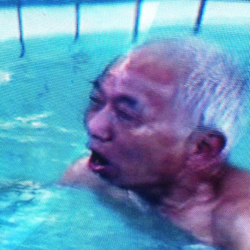 这位上了年纪头发全白的老伯正在冰冷的池水中游泳图片
